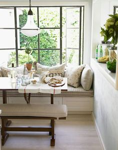 """again, love the iron    A Comfortable Breakfast Nook  Barrett created a banquette """"to add a comfort zone to the kitchen."""" She upholstered it in Rogers & Goffigon's Pandora in Greggio. Print pillows are from C Geller Pillows. The antique pendant light is from Rewire."""