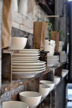 Clean white plates and bowls set against a pretty patina background.
