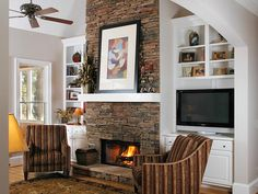Cozy Comfort    This stacked-stone, floor-to-ceiling fireplace comes alive against the crisp, white mantel and bookcases. The shades of the stone are repeated in the stripes of the chairs that flank the fireplace opening