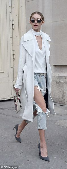 Stylish departure: Gigi's exit style was a lot less formal as she braved the cold to flash the flesh in extremely ripped skinny jeans, which she paired with a white blouse that featured keyhole detailing and a coordinating trench coat