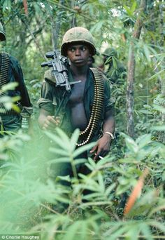 A machine gun operator walking through the jungle weighed down with guns and ammunition in Viet Nam