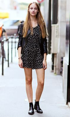 Black leather moto jacket worn over a printed mini dress and paired with black ankle boots
