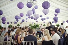 Lavender and purple paper lanterns hang in a white tented venue with a draped ceiling at a wedding reception.