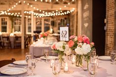 Mikkel Paige Photography photos from a wedding reception at The Stockroom at 230 in Raleigh. A picture of the centerpieces with green, white and coral flowers and Rifle Paper Co table numbers.