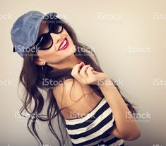 Enjoyment young woman in sunglasses and blue baseball cap posing and looking with smile in striped blouse. Closeup happy portrait. Toned vintage portrait royalty-free stock photo