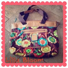 Lilly Bloom Handbag Made of nylon material. This is such a vibrant , beautiful floral patterned bag. It is very spacious & has one zippered pocket on inside. This bag is reversible. Inside is a turquoise color with no tears or stains. Used once. Like-New condition! Lilly Bloom Bags