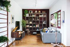 Estante metálica com prateleira de madeira, sofá cinza com almofadas coloridas e parede pintada em tom de beringela.