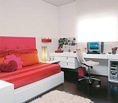 """Para a irmã mais nova, de 7 anos, o arquiteto Toninho Noronha seguiu os mesmos moldes do quarto anterior: cama com bicama, bancada de estudo, paredes revestidas a meia altura de madeira laqueada e módulos para guardar roupas e brinquedos. """"Mudei apenas as cores: rosa e laranja, conforme o pedido da caçula"""", lembra. Na cabeceira, de 75 cm de altura, um toque inusitado: a lycra forra o painel de madeira e espuma."""