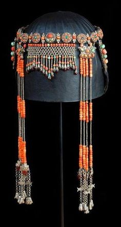 Headdress of Ordos Mongolian married woman, with extensive fringe following the line of the eyebrows. China, Inner Mongolia: Ordos people; 19th/20th c. Height (total): 39 cm. Silver, coral, Peking glass, turquoise, malachite, agate, enamel, cloth. Published in Truus Daalder, *Ethnic Jewellery and Adornment*, p. 278. (Joost Daalder).