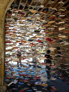 """Suspended Books Magically Fill Swiss Tunnel - The village of """"Romainmôtier holds a charming annual used book fair. . . In 2005, Swiss artist Jan Reymond began constructing elaborate installations each year, made of the old, unsold books as a last hurrah for the soon-to-be discarded objects . . . Many of Reymond's book installations mimic the church and quaint town's round arches and stained glass fixtures . . .""""  (click on the link to see more images)"""