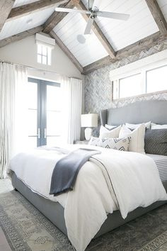 Master Bedroom. This master bedroom feels very original. Gray bedroom boasts a vaulted paneled ceiling adorned with rustic wood trim over a gray herringbone tiled accent wall lined with a gray wingback headboard on bed dressed in white and grey bedding atop a gray rug placed in front of black framed French doors dressed in white drapes. Plank Ceiling Paint Color: Dunn Edwards 2005 Evershield Eggshell.  The master bedroom also has vaulted ceilings and French doors to a balcony. Master…