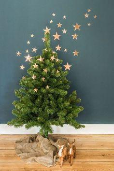 De la toile de jute et des cerfs décorent le pied du sapin à Noël.