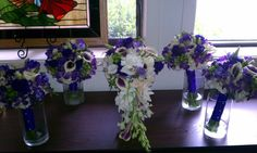 """Middle Bouquet: Cascade Style with """"Picasso"""" Mini Calla Lilies, White Mini Calla Lillies, White Dendrbium Orchids, Ivory Roses, Gardenias, Purple Lisisnathus, Purple Freeisa, and Green Coffee Berry  Hand Tied Bouquets: Picasso Mini Calla Lilies, Green Coffee Berry, Purple Lisianthus, Purple Freesia, and White Hydrangea"""