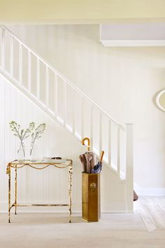 Dress up a stairwell wall by attaching tongue-in-groove paneling. A vintage brass console table shines with pretty accessories; pairs with brass umbrella stand. Home Entrance Decor, Home Decor, Entrance Hall, Stair Paneling, Stairwell Wall, Brass Console Table, Tongue And Groove Panelling, Under Stairs Cupboard, Home Office Space