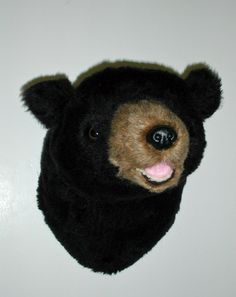 """Plush Black Bear Head """"Harry"""" Small Shoulder Mount. Our little bears all love celebrating. They enjoy wearing headbands, hats, bandannas, and bow ties! As with all our smaller bears, Harry's fur is a shorter pile than his big brothers. However, his small size makes him a perfect addition to a den, office or children's room. He has a sweet smile showing just the tip of his little tongue. PRODUCT SPECS: Ready to hang. Harry's depth is 12"""""""" from nose to wall. Girth at shoulder is 24""""."""