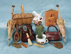 Theriault's Antique Doll Auctions - Collection of Accessories - Including wooden-handled parasol with figural grip & original rose silk cover; another parasol, porcelain pitcher and pot berry and floral design, celluloid hanging mirror w/ accessories including miniature celluloid whisk broom,green leather gloves,leather purse with bail handle,two mesh purses,wood-frame hand mirror,wooden comb, double-sided basket,and celluloid comb. Late 19/early-20th century