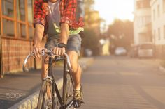 Close up hipster on bike in the city at sunset. Shot with sunflare and without…