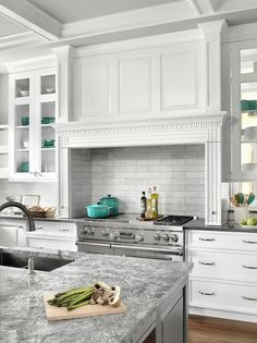 Stunning white and gray kitchen features glass paneled white cabinets positioned flanking a linear wainscoted hood accented with a white trim framing an alcove fitted with linear marble backsplash tiles and mounted above a stainless steel dual range.