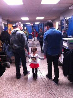 Tyler and Dylan holding hands with one of their youngest fans.