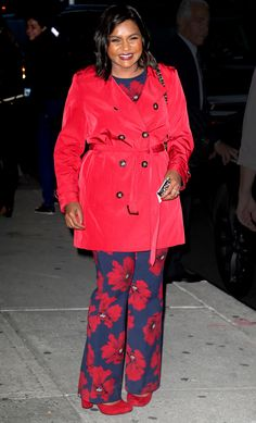 Mindy Kaling in a red trench coat and floral pants