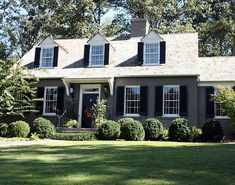 Traditional home given a makeover with painted brick, white trim, and black shutters.