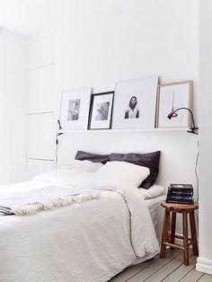 decoração de quarto branco com prateleira com quadros na cabeceira da cama, banco como criado mudo, livros e luminárias presas na prateleira