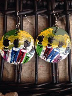 These beautiful hand made earrings are by Ugandan artist, Davis Muwumba. They are made using recycled bottle caps Davis hammered down and then