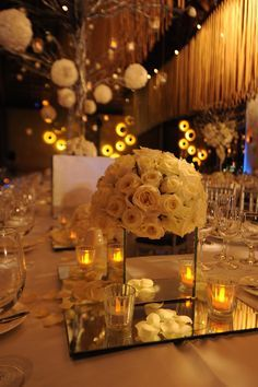 Centro de mesa con base cuadra de espejo con rosa sobre espejo.
