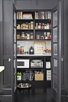 Deep pantry shelves enclosed by French doors create a designated space for small appliances, like a microwave and toaster, to avoid cluttered counter space.