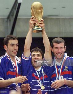 French forward Robert Pires is flanked by defender Bixente Lizarazu (L) and midfielder Zinedine Zidane (R) as he holds the FIFA trophy 12 July at the Stade de France in Saint-Denis, near Paris, after France defeated Brazil 3-0 in the 1998 Soccer World Cup final.