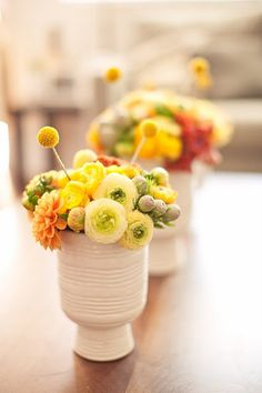 "Modern centerpieces - a mix of textured white ceramic vases filled with colorful dahlias, ranunculas and tulips, and finished by ""antennae"" made of yellow billy balls."