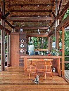 Integrada à sala, a cozinha fca isolada pelo balcão de itaúba, mesma madeira do piso, fnalizado com resina fosca.