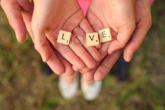 verloofden houden samen verlovingsring vast met scrabble letters love in natuurgebied tijdens fotoshoot