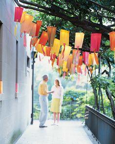DIY Lanterns. Beribboned colored bags hung from lights make fun lanterns.