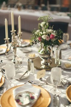 A tablescape filled with gold charger plates, white linens, frosted wine glasses and polished silver centerpieces of tulips, roses and greenery deserves to be at every elegant wedding. {Rife Ponce Photography}