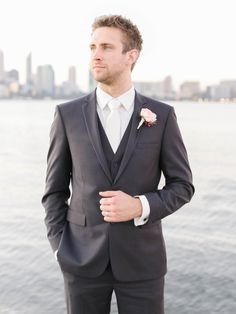 Photography: Katie Grant   www.katiegrantphoto.com   View more: http://stylemepretty.com/vault/gallery/39093  Handsome groom, charcoal suit, Perth skyline, wedding, romantic, pink rose