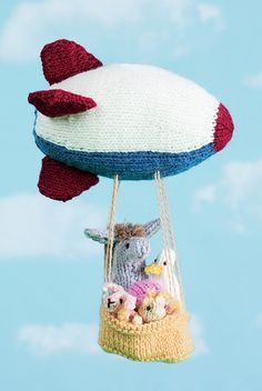 Knitting Pattern for Zeppelin Mobile With Animal Passengers - Donkey, goose, bunny, and human aviatrix soar away in the basket of their zeppelin. The passengers can be taken out of the basket. Suitable for all ages as a mobile hung out of children's reach; suitable for ages 8 and up as a toy. One of the 24 patterns in Knit and Crochet Toys, 2017. Designed by Sachiyo Ishii. Size 6″ from zeppelin nose to tail, and 8″ tall from top of zeppelin to bottom of basket