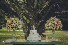 Mesa bolo e doces com arranjos repletos de cor
