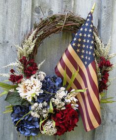 Americana Wreath - Lush Hydrangeas and mums in deep hues of navy blue, dark red and creamy ivory blend harmoniously with a tea-stained American flag all set upon a grapevine wreath to create this stunning tribute to America.