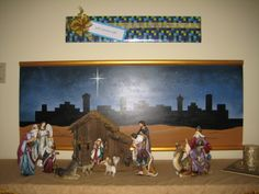 "This is a photo of the new nativity that Mark and I bought this year.  He helped me paint the backdrop and then because the scene needed height, I wrapped the gift to hang above.....The tag reads ""God's Greatest Gift"".  God sending His Only Begotten Son to redeem all of mankind  surely is the greatest gift!"