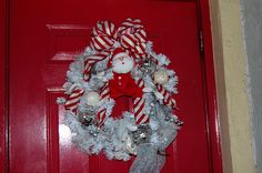White Christmas wreath with silver, white and red decor. The santa is a dog toy!