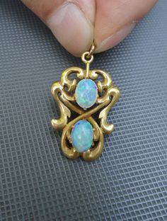 This is a very nice opal pendant from early 1900s. Nice period scroll work. 1 1/8 inches long, and total 4.3 grams. Not signed, but tested 14K.