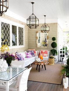 """Gorgeous funky patio design with iron glass geometric lanterns, white slip-covered sectional sofa, yellow orange gunmetal stool, jute rug, pink purple red pillows from Quadrille & Cowtan & Tout. and Restoration hardware topiaries."" decorpad"