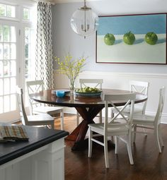 Fun contemporary dining room design with; chair rail and beadboard, crossed legs round wood dining table, white x-back wood chairs, clear glass pendant light, & blue & brown geometric curtains in window panels. ~Muse Interiors