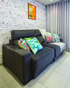 O sofá retrátil e robusto dá conforto aos momentos de relax. A atmosfera descontraída fica por conta do papel de parede de tijolinhos, almofadas coloridas e divertidas, assim como o pôster na parede.