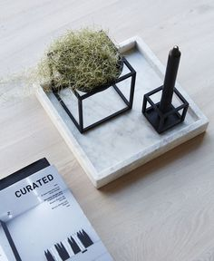Square Italian Carrara marble tray featured with a By Lassen small black Kubus…