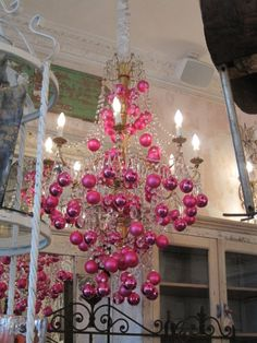 Chandelier with pink Christmas ornaments.