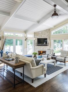 Bright living room with white bead board ceiling, stone fireplace, large windows, dark wood floors | Kim E Courtney Interior Design