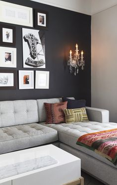 black wall + art grouping + sconce + grey sectional