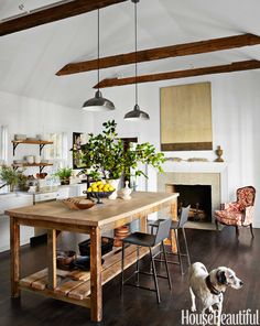 A new kitchen looks lived-in thanks to the reclaimed wood on the island, beams, and shelves. Vintage armchair covered in a Barclay Butera fabric. Phoenix Carbon stools, CB2. Pendants, Home Depot.   - HouseBeautiful.com